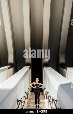 Giovane donna in piedi su per le scale Foto Stock