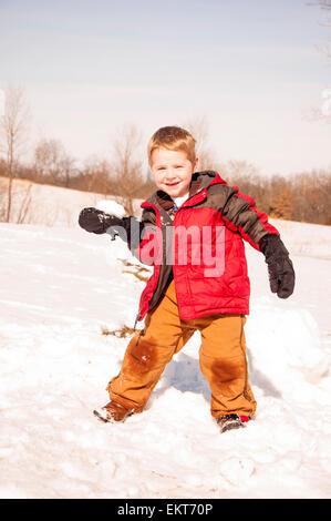 Ragazzo pronto a lanciare palle di neve Foto Stock