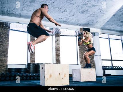 L uomo e la donna il salto sulla casella adatta alla palestra Foto Stock