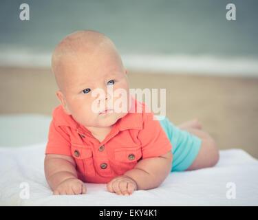 Carino il bambino posa sul lettino in spiaggia Foto Stock