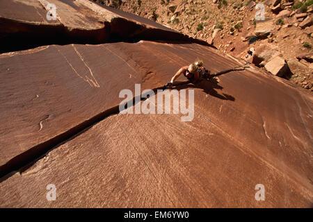 Un rocciatore sulle sole blu 5.0; Indian Creek, Utah, Stati Uniti d'America Foto Stock