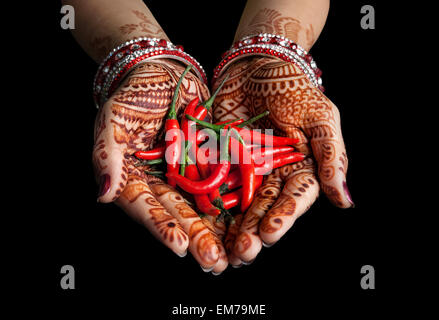 Donna mani con henna holding peperoncino rosso isolato su sfondo nero con tracciato di ritaglio Foto Stock