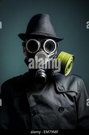 Uomo in maschera a gas, impermeabile e cappello nero a sfondo scuro Foto Stock