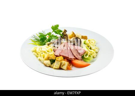 Insalata con prosciutto, funghi, pomodori e pasta su uno sfondo isolato Foto Stock