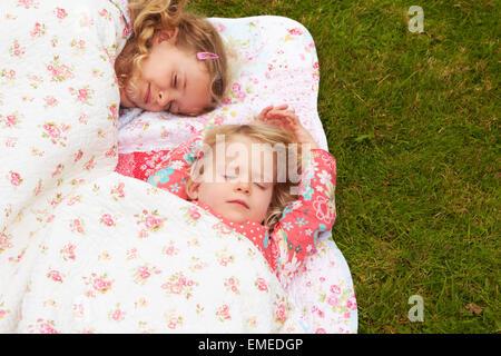 Due ragazze giacente sotto la coperta in vacanza in campeggio Foto Stock