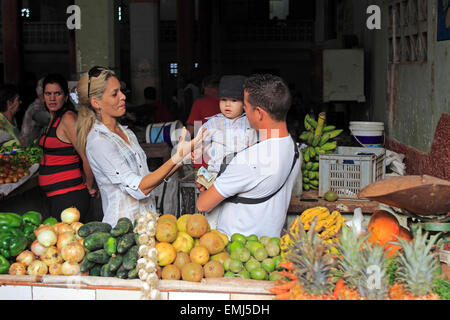Giovane famiglia cubana nel mercato di frutta e verdura che mostra i prodotti disponibili per la vendita a Cienfuegos Cuba