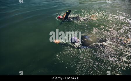 Vista dall'alto di atleti di praticare il nuoto per la gara di triathlon. Formazione del Triathlon in acque aperte. Foto Stock