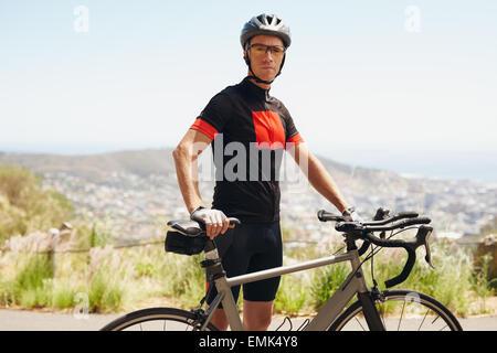 Ritratto di montare il giovane uomo in piedi con la sua bicicletta, all'esterno. Prendendo una pausa dopo un allenamento Foto Stock