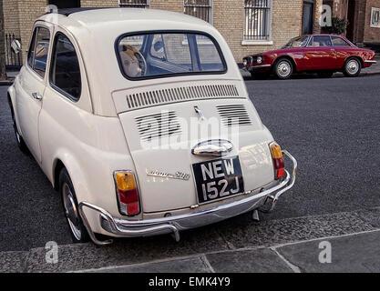 Anni sessanta Fiat 500 e Alfa Romeo Giulia Sprint parcheggiato sulla strada a Londra REGNO UNITO Foto Stock