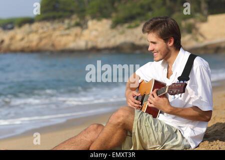 Uomo bello suonare la chitarra classica seduto sulla spiaggia in vacanza Foto Stock