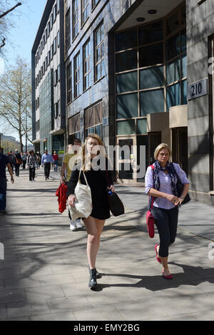 Giovane donna & donna anziana camminando sul marciapiede in Londra Foto Stock