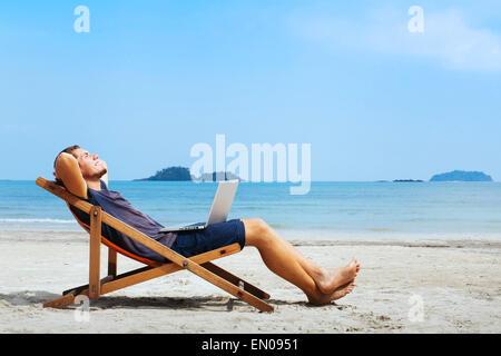 Imprenditore sorridente con il computer in relax sulla spiaggia Foto Stock