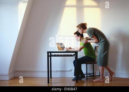 Coppia giovane guardando il laptop a casa loro in interni luminosi Foto Stock