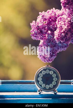 Ramo di fiore lilla su vintage elegante orologio in corrispondenza della finestra. Luce naturale. Foto Stock