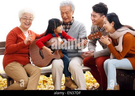 La famiglia felice outdoor suonare la chitarra Foto Stock