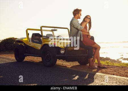 Amorevole coppia giovane seduto sul cofano della loro auto mentre su roadtrip. Giovani caucasici giovane rilassante Foto Stock