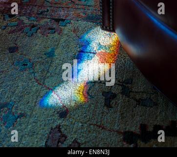 Fine giornata la luce solare rifratta attraverso un macchiato, vetrate a piombo crea un prisma di colore sulla moquette Foto Stock