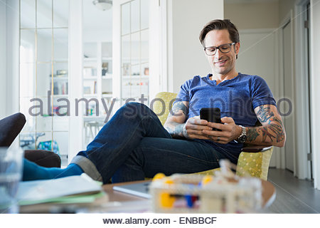 Uomo rilassato con tatuaggi texting in salotto Foto Stock