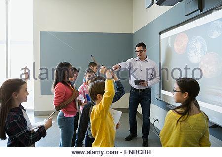 Gli studenti a porre domande di docente leader lezione di astronomia Foto Stock