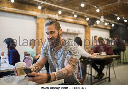 Uomo Barbuto con tatuaggi di bere il caffè nella caffetteria Foto Stock