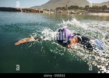 Concorrente maschio nuota freestyle nell'acqua. Atleta maschio nuoto su una concorrenza triathletic. Foto Stock