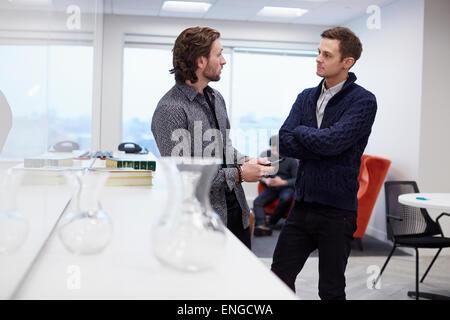 Due uomini in un ufficio permanente e la conversazione, uno con le braccia piegate. Foto Stock