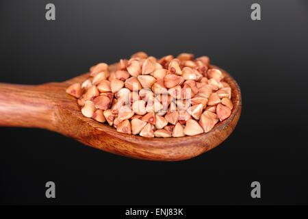 Il grano saraceno in cucchiaio di legno su sfondo nero Foto Stock