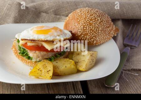 Cheeseburger con uovo fritto e patate vedges orizzontale messa a fuoco selettiva Foto Stock