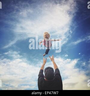 Padre gettando il suo figlio in aria Foto Stock