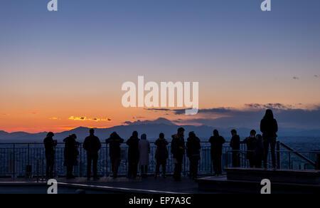 I turisti si affacciano sul paesaggio urbano di Tokyo e il Monte Fuji nella distanza come il sole tramonta su Gennaio Foto Stock