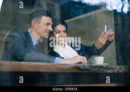 Imprenditrice sorridente e imprenditore rendendo selfie foto sullo smartphone in cafe Foto Stock