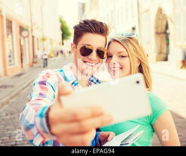 Coppia sorridente con lo smartphone in città Foto Stock