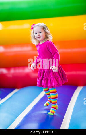 Carino divertente asilo bambina giocando, salta e rimbalza in un castello gonfiabile alla festa di compleanno in Foto Stock