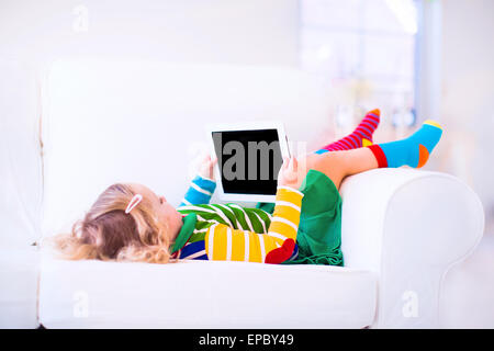 Divertenti piccole toddler ragazza con tablet pc relax su un lettino bianco Foto Stock