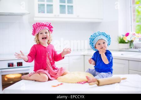Carino kids, adorabile bambina e divertenti baby boy indossando i colori rosa e blu chef cappelli giocando con la Foto Stock