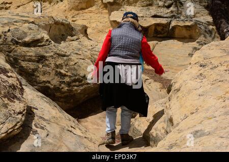 Senior Citizen negoziando scale scavate nella pietra arenaria, El Morro Monumento Nazionale New Mexico - USA Foto Stock