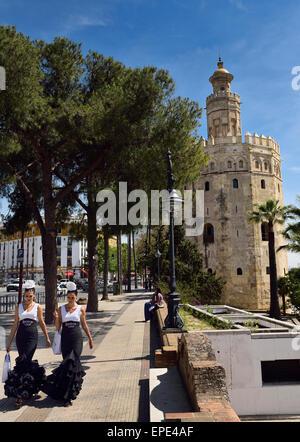 Due giovani donne in abiti di flamenco a piedi lungo Christopher Columbus Avenue con Torre del Oro a Siviglia Foto Stock
