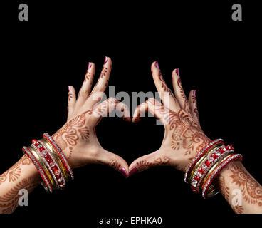 Donna mani con henna fare cuore gesto isolato su sfondo nero con tracciato di ritaglio Foto Stock