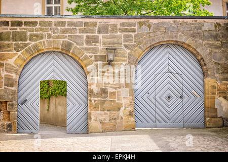 Immagine con due porte in una parete dove un cancello viene aperto, l'altra è chiusa. Foto Stock