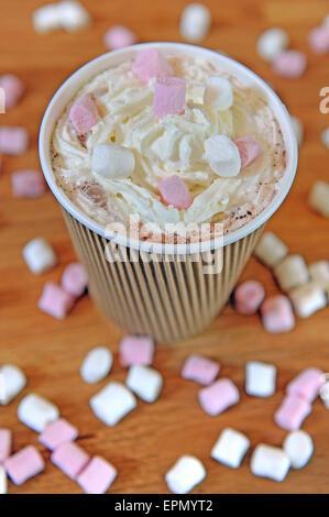 Studio shot di marrone triple carta rigata tazza da caffè riempito con cioccolata calda, panna montata e mini marshmallows. Foto Stock