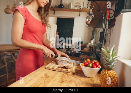 Tagliate il colpo di una giovane donna di tranciatura di un sfornato fresco della pagnotta di pane su una cucina Foto Stock