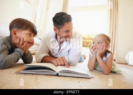Piscina colpo di giovane con due bambini la lettura di un libro di storia. Famiglia sdraiato sul pavimento con un Foto Stock