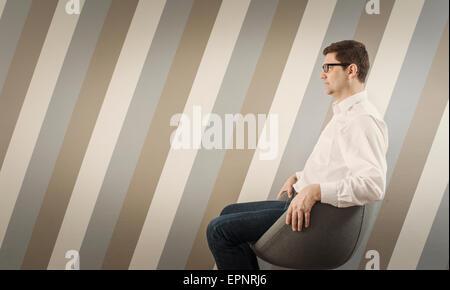 Ritratto di pensieroso uomo seduto e in attesa su una sedia nel corridoio. Foto Stock