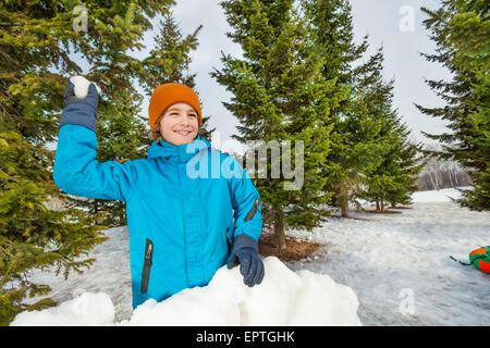 Ragazzo pronto a lanciare palle di neve durante il gioco Foto Stock