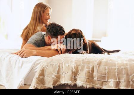 Colpo di una giovane coppia rilassante sul letto con il suo cane. Giovane uomo e donna in camera da letto a giocare Foto Stock