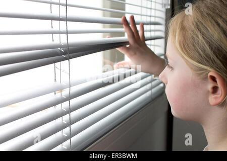 Ragazza cerca attraverso le persiane della finestra Foto Stock