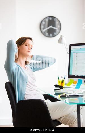La donna che soffre di dolori al collo in ufficio.