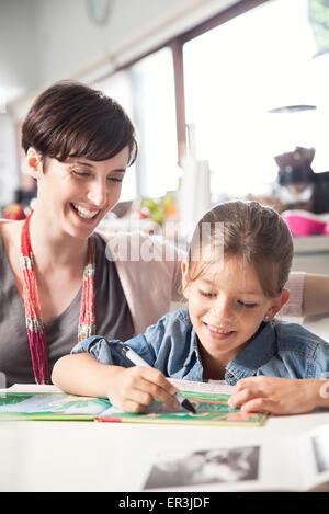 Insegnamento madre giovane figlia di leggere Foto Stock