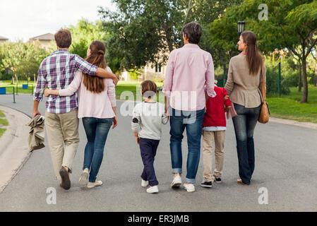 Famiglia camminare insieme nella strada, vista posteriore Foto Stock