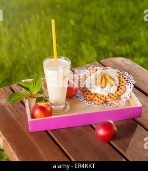 Waffle e frullato sul tavolo di legno nel giardino. Debica, Polonia Foto Stock